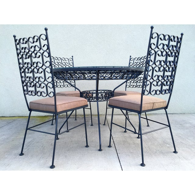 "Arthur Umanoff wrought iron five-piece dinette set. Includes a 42"" round table with a glass tabletop and four chairs with..."