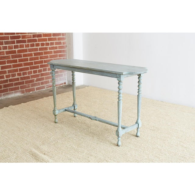 Vintage console or sofa table featuring a distressed painted finish in a lovely robin's egg blue color. Rounded on both...