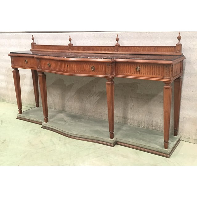 About French Louis XVI style free standing console or sofa table with three drawers, fluted legs and a black marble top,...