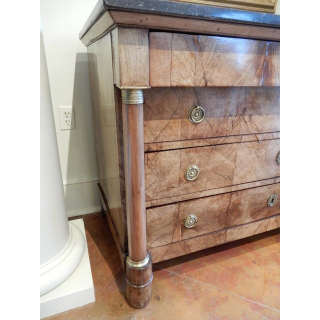 Beautiful circa 1810 French Empire walnut commode with a black marble top. The commode has four drawers. It has been...