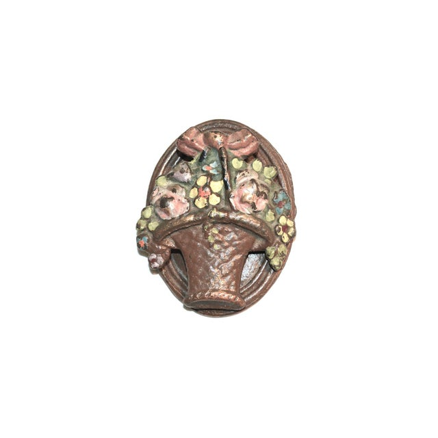 A 1920s iron door knocker featuring a basketful of flowers with a bow on top. Original enamel is chippy and charming. A...