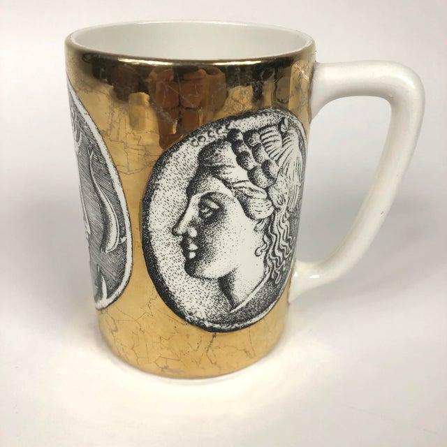 Large Porcelain Coffee Mug by Piero Fornasetti depicting black and white Roman Faces on gold/ gilt background. Profili...