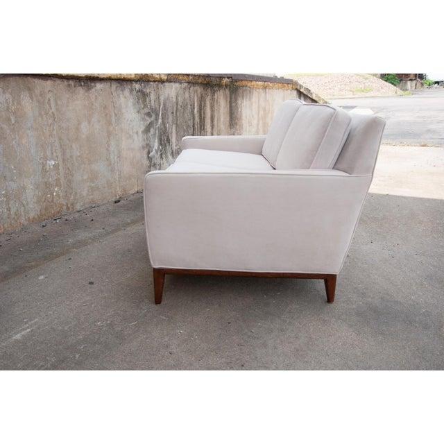 An elegant pair of modern upholstered sofas in a cream colored velvet inspired by the designs of Dunbar and John Stuart....