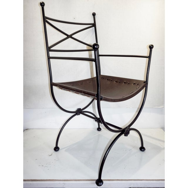 "This is a pair of Italian iron and leather curule chairs, circa 1960. Each one features an ""X"" shaped backrest and..."