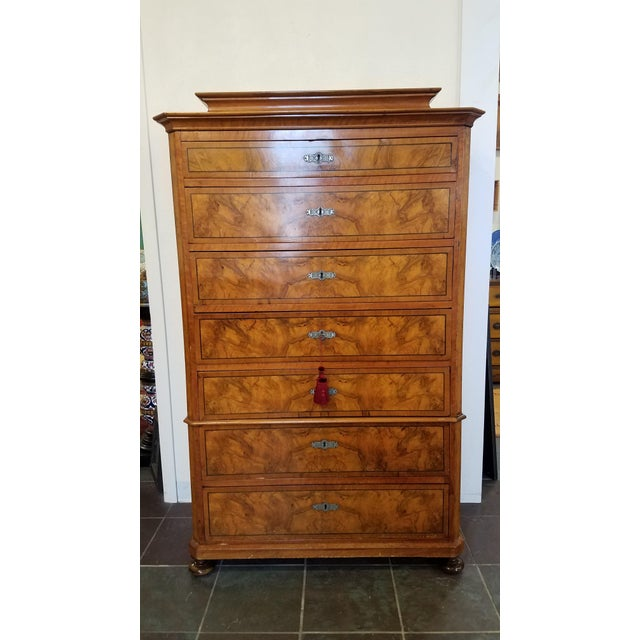 This late 19th century continental burlwood semainier features seven, fully functional, graduated drawers. It is a...