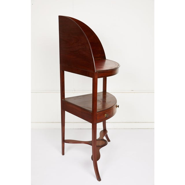 Late 19th century corner washstand of mahogany with a demiluned gallery behind a red leather embossed top shelf and inlaid...