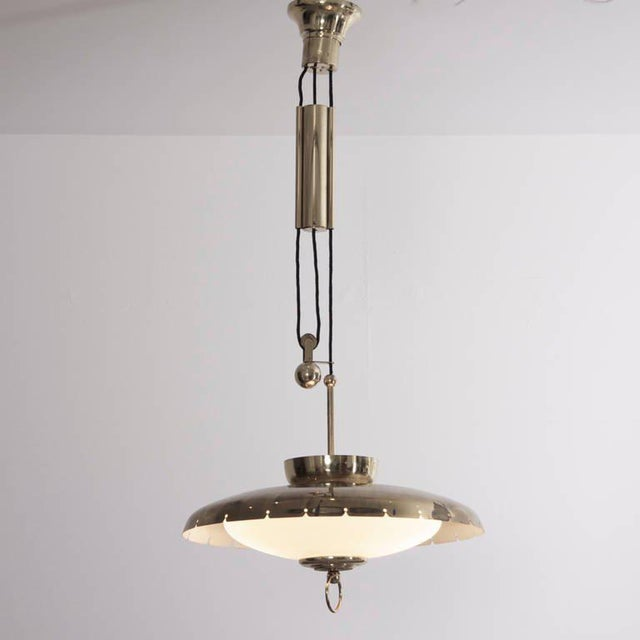 Beautiful brass Italian chandelier manufactered in the Fifties. Brass mounts and counterweight with brass shade and...