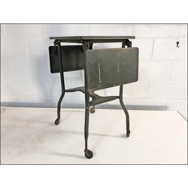 VINTAGE TYPEWRITER TABLE. Original drab green paint. The piece dates to the 1950s/60s. Rolls on (4) original caster...