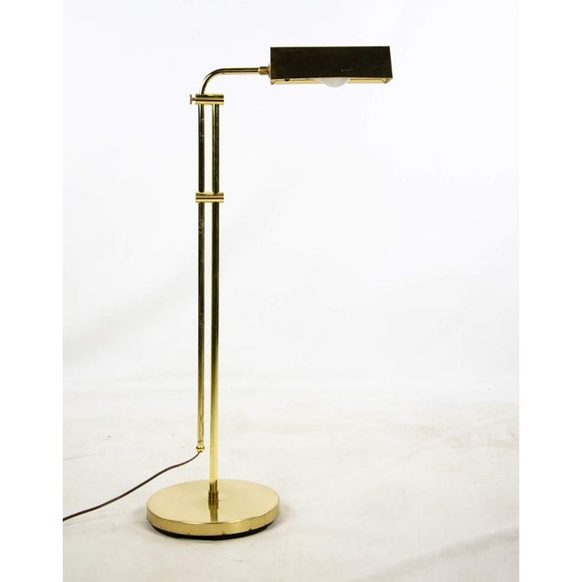 A modern twist on the classic pharmacy lamp, this contemporary Mid Century Style brass-finished adjustable floor lamp...