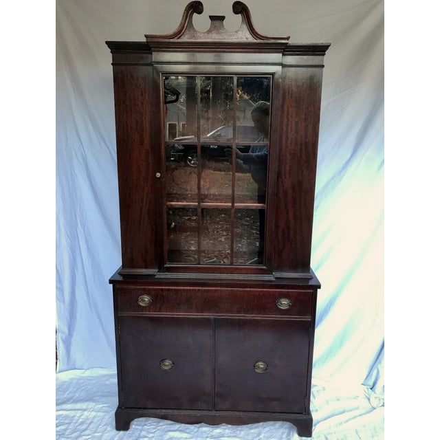 A gorgeous mahogany china cabinet with one drawer and a pair of doors that open up to a cabinet space with one removable...