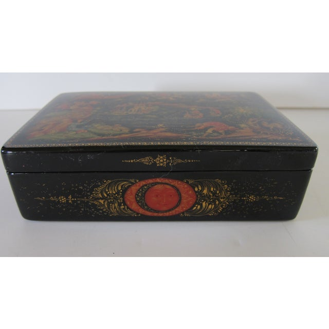 Russian black lacquered box that is hinged at the back and has a red lacquer interior. The top is hand painted in...