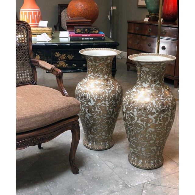 Each strikingly large porcelain vase hand-painted with richly-decorated gilt floral vines on a white ground; with...