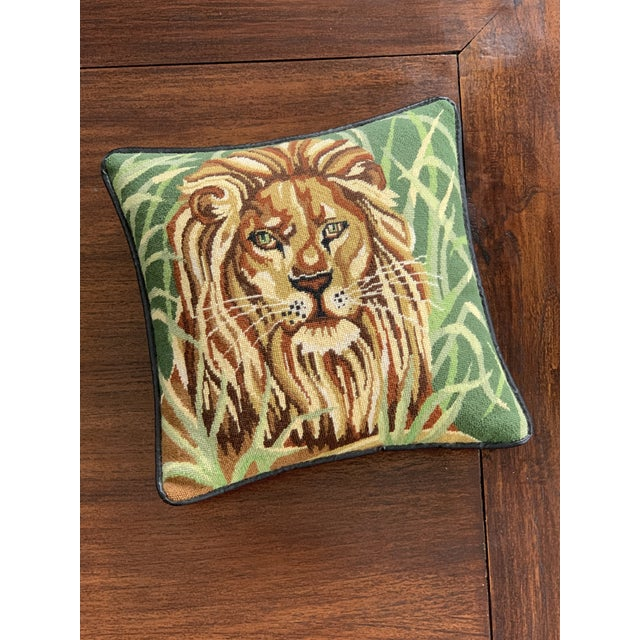 Vintage Mid Century needlepoint pillow featuring a lion with jungle background, black vinyl backing imitating leather....