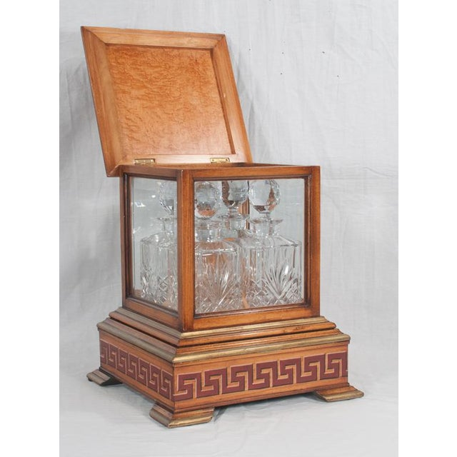 A Georgian style walnut tantalus set with pagoda top having scroll and mask decorations on the top, grecian key decoration...