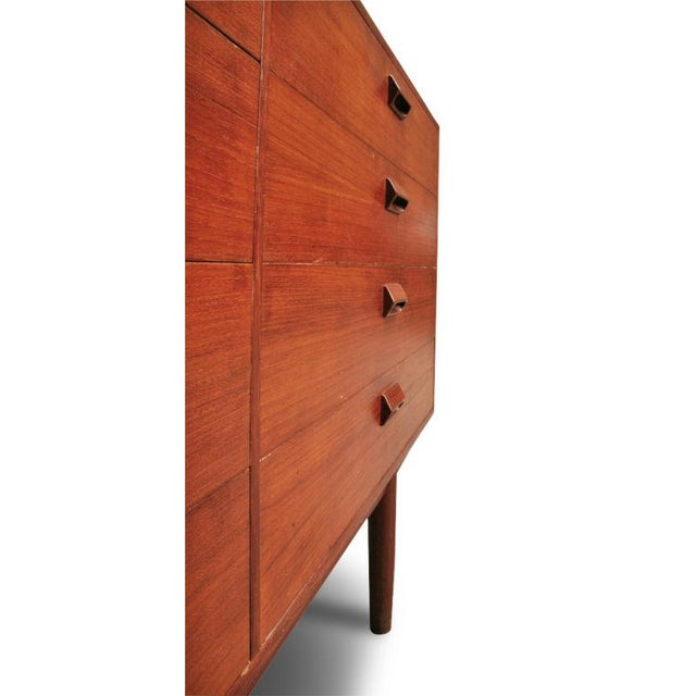 An inviting chest of drawers in teak comprising eight side-by-side drawers each with integral wood handles, the whole...