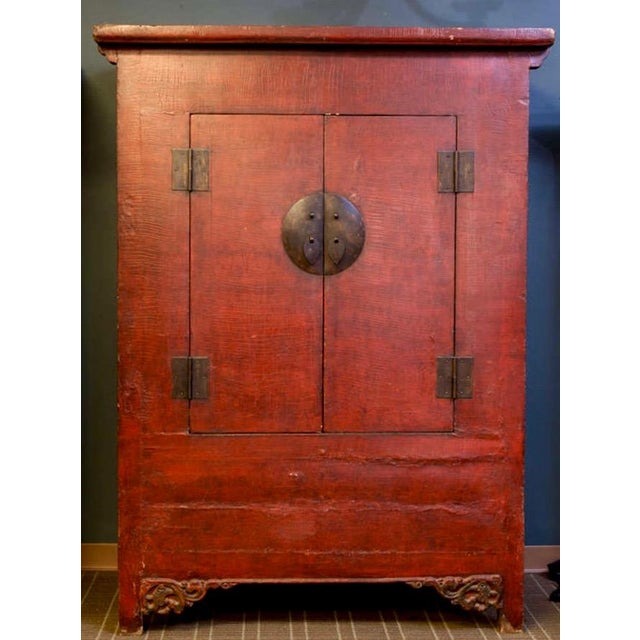Circa 1900 large Chinese wood cabinet with red lacquer finish, brass hardware, hinged front doors and two internal...