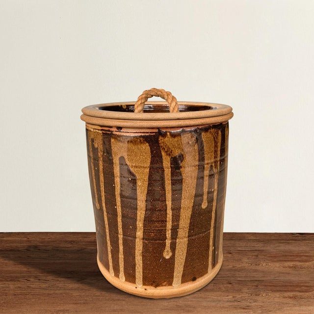 A wonderful vintage American studio pottery lidded jar with a fantastic brown and tan drip-glaze pattern with a rope-...