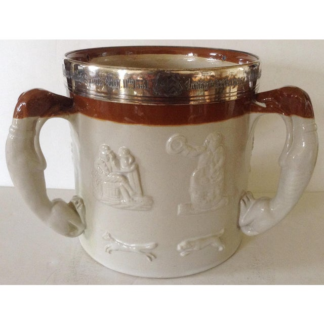Merton College sports presentation tyg fashioned with three fox hound handles and an engraved sterling rim dated 1881....