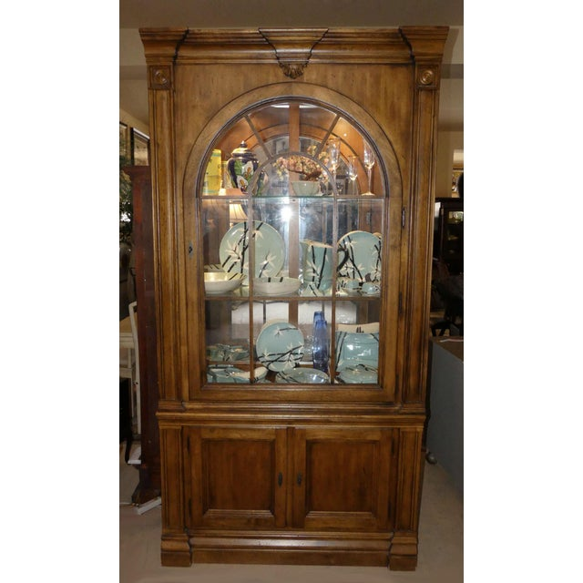 Lexington Furniture Southern Living Collection lighted china display cabinet. Features an arched wood framed glass door...