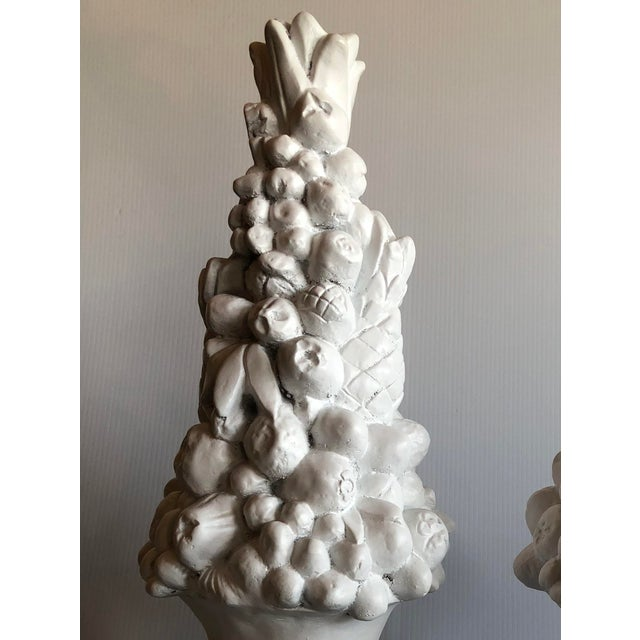 Plaster fruit topiaries planted in plaster urns. Finished in white gesso. Depth and width given are at widest part.