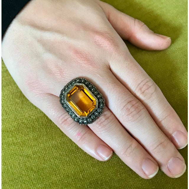 Circa 1930s to 1940 large sterling silver ring set with a faceted topaz-glass stone surrounded with marcasites. The ring...