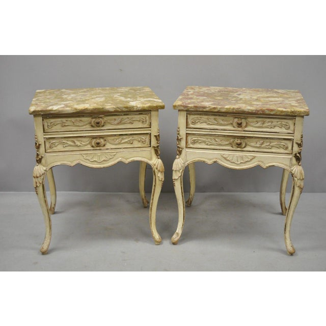 Pair of vintage distress painted French Louis XV style marble top end tables by Danby. Item features carved wood shells on...