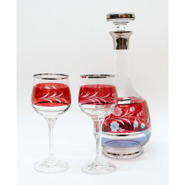 Beautiful red and blue flash decanter and 2 cordial glasses that have etched flowers and leafs motif with silver trim. One...