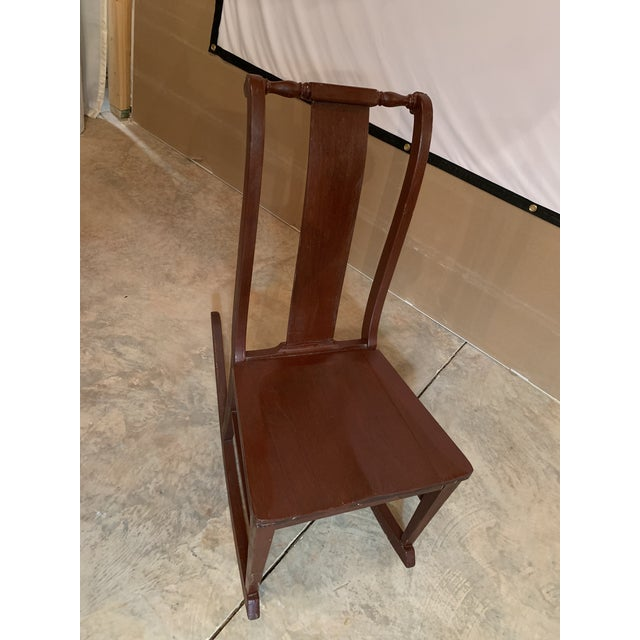 Antique carved scrolled splat back solid wood child's rocking chair. Has been painted brown with vintage exterior paint....