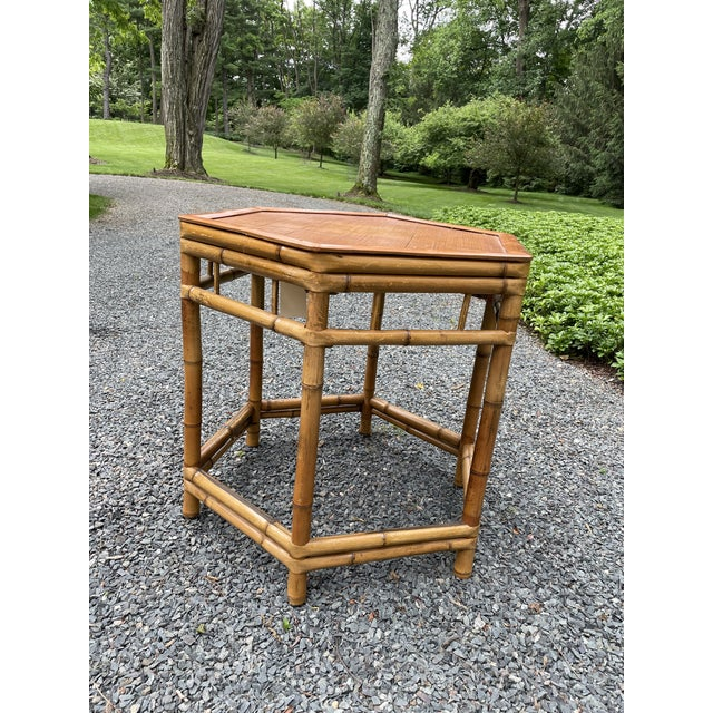 A mid-century bamboo side table in an octagonal shape. The table has a split reed top and the body of the table is...