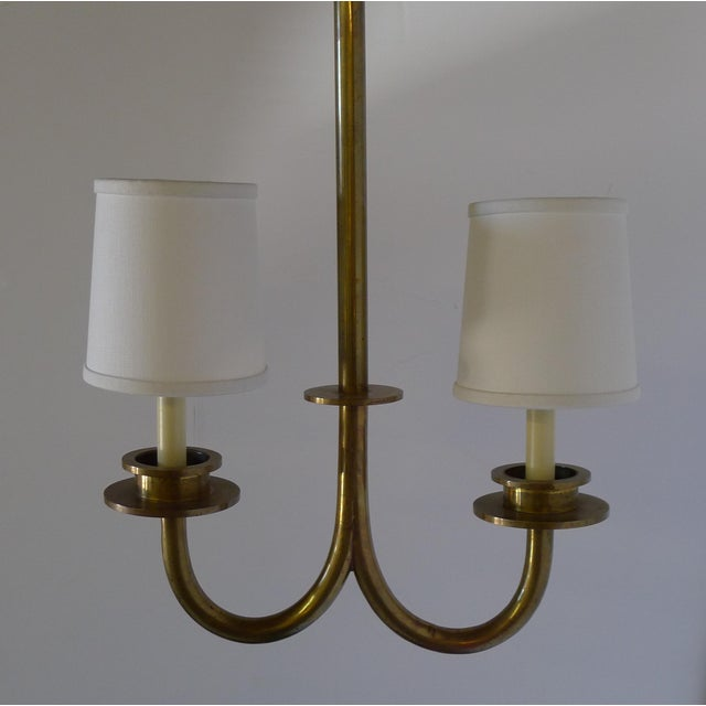 "Restored asymmetrical two light brass pendant with shades. The fixture is 16""w and 25""h, with overall drop height of 4'h..."