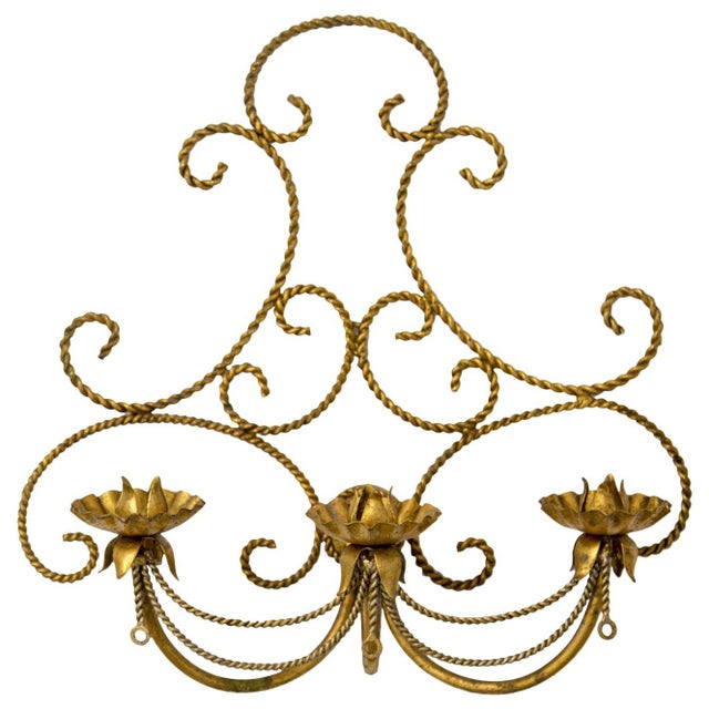 Vintage Italian tolewear three-candle wall sconce with intentionally distressed and aged gilded finish. It is made up of...