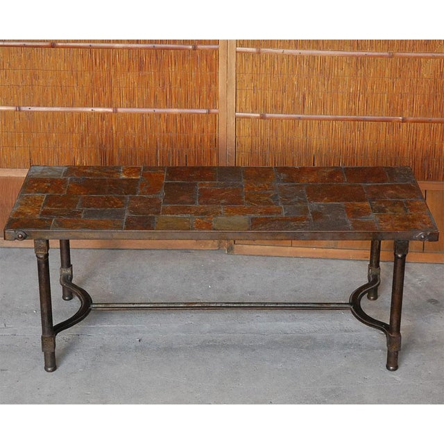 Slate top coffee table with metal base by Jacques Adnet. Note the different colors of the slate and the beautiful iron job!