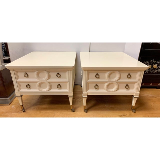 Matching pair of two drawer bedside tables nightstands on brass castors in an off white lacquer finish. Dovetailed drawers...