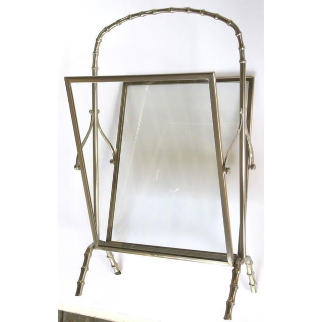 A chic and stylish French Masion Bagues 1940's chrome and glass faux bamboo magazine rack; with arching faux bamboo handle...