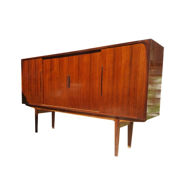A beautiful Scandinavian rosewood buffet. Made in the 1960s. Features 4 sliding doors, 4 shelves, 8 drawers and 1 bar...