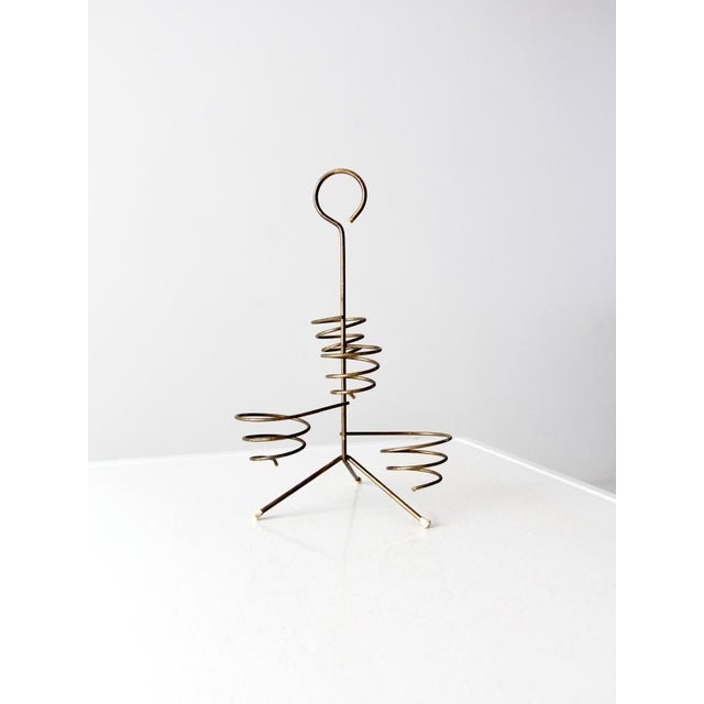 This is a mid-century brass coil stand. The desk or kitchen organizer features four coil spring baskets with tripod legs...