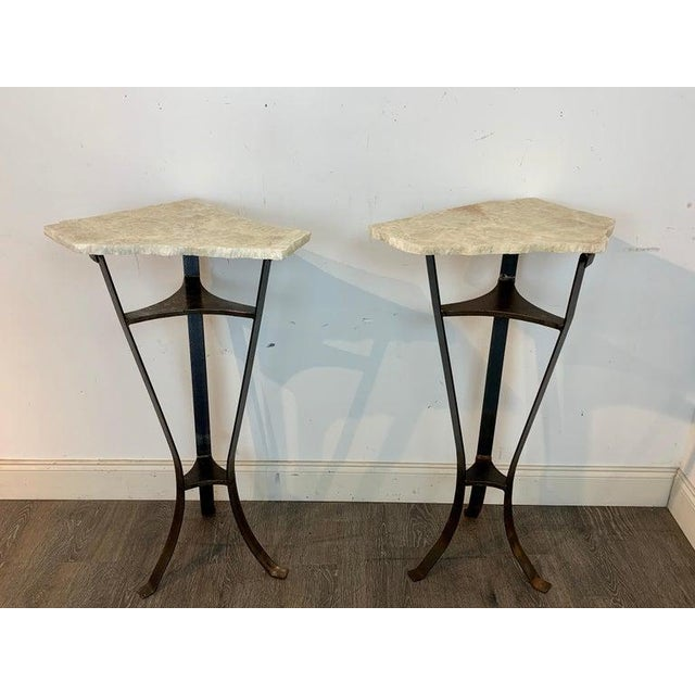 A pair of rock crystal and iron pedestals, each one with a live edge slab of rock crystal / quartz raised on a tripartite,...