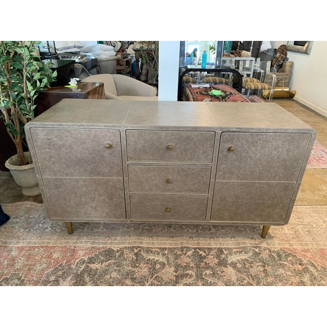 Finished in natural, full-grain leather, this graceful and sophisticated buffet cabinet from Made Goods has rounded...