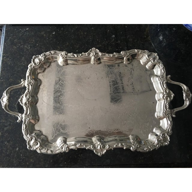 This is a Victorian silver-plate, footed butler's tray with double handles. Very ornate embossed edge and etched center....