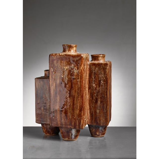 A large brown glazed ceramic vase. This sculptural piece has the shape of three vases fused together and has a very strong...