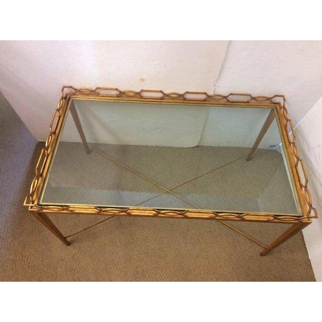 Medium sized rectangular gilt iron coffee table having stylish geometric link gallery around the glass top and elegant...