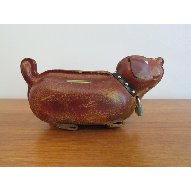 This mid-century brown leather dog coin bank closes up with a pad lock, keeping one's pennies and quarters super secure,...