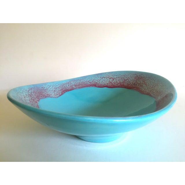 This vintage Mid Century Modern studio pottery aqua blue drip glaze oval ellipse ceramic pedestal bowl is a very special...