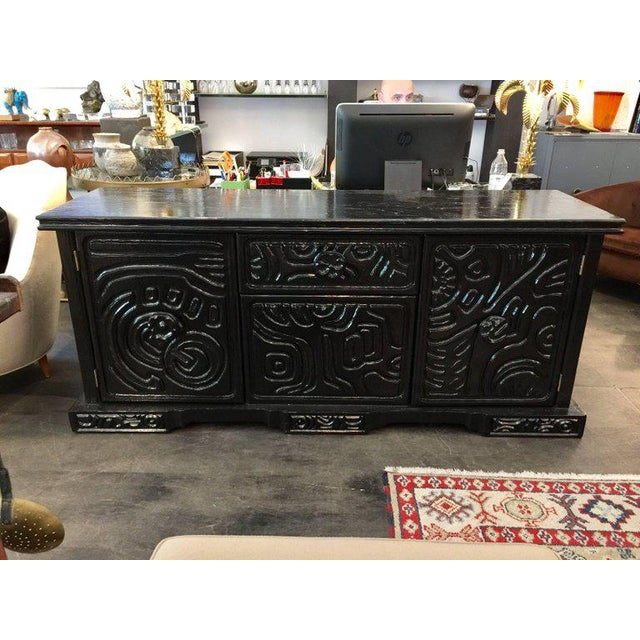 Lacquered in a black piano finish the brutal carved wood design is almost tribal and artistic (reminiscent of Louise...