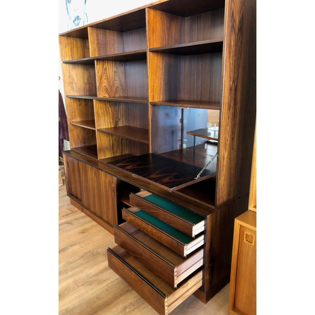 Vintage Danish rosewood display with adjustable shelving, drawers, and a drop-leaf bar with key. In very good vintage...