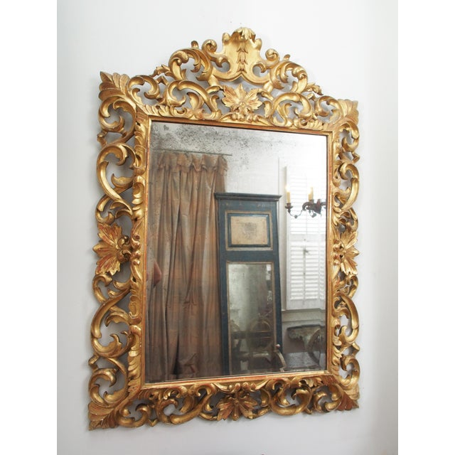 A beveled mirror with a pierced frame of carved and gilded wood, centered with a simple crest and having bellflowers,...