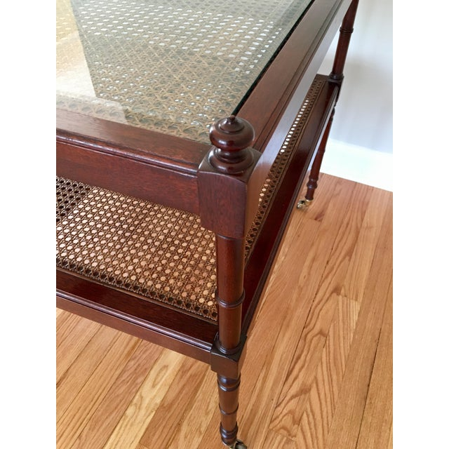 A gorgeous mahogany and cane rolling table made by Baker Furniture. This table is in beautiful vintage condition showing...