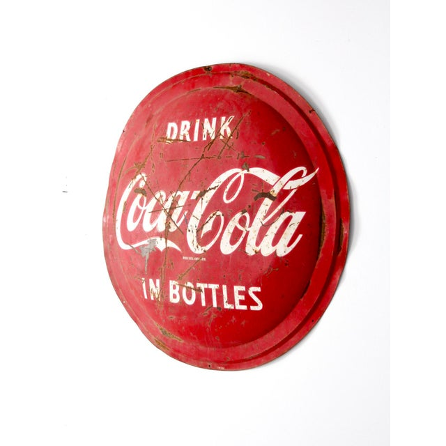 """This is a classic Coca-Cola button sign circa 1957. The round red metal sign features the """"Drink Coca-Cola in Bottles""""..."""