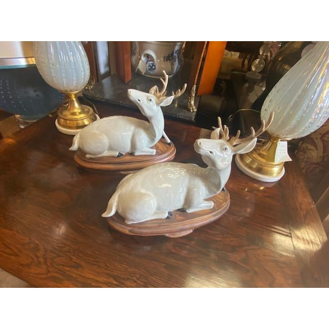 Pair of Vintage Porcelain Deer Figurine. seated on wooden base. great decoration for holliday season.