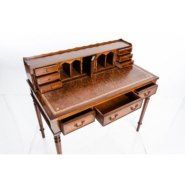 Antique ladies writing desk with a replaced leather top. Nine working drawers and five pigeon holes. Writing surface is 30...